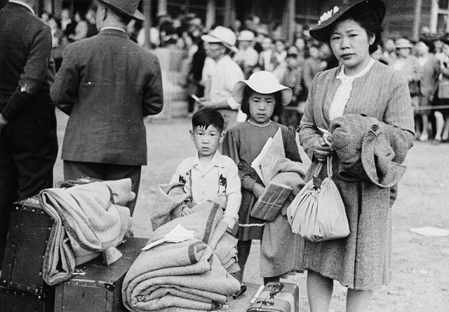 Japanese-Canadian woman, girl and boy wait to be relocated to a camp in the interior of British Columbia, 1942. Library and Archives Canada